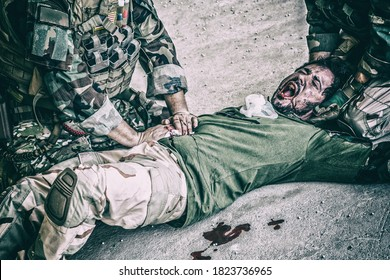 Soldiers trying to stop bleeding at wounded comrade who lying on floor, suffering and screaming in paine. Commando fighter pressing with hands on bloody wound at friends stomach, giving emergency care