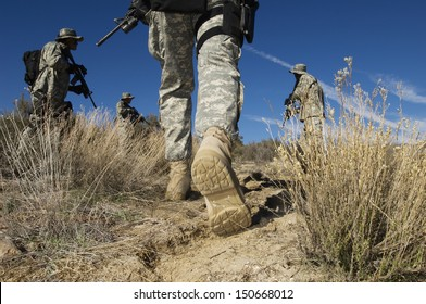 Soldiers walking in desert, low section