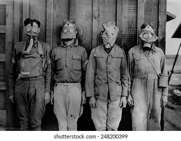 Soldiers wearing WW1 gas masks. L-R: American, British. French, German. 1917-18.