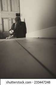 A Sole Figure Crouched Down in the Corner of a Room
