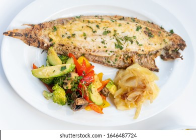 Sole meunière fish with grilled vegetables and caramelized onions on a white plate with white background