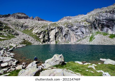 A sole hiker resting close to the shore of Llosás lake, one of the most amazing spots of the Pyrenees Mountains, Spain (no model release attached as the person on the picture can not be recognized).