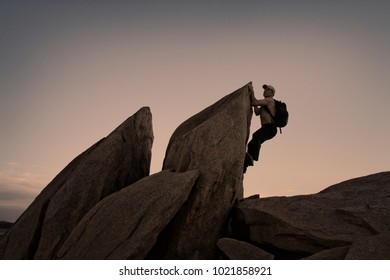 Sole Male Rock Climbing at Sunset in Folsom, California.