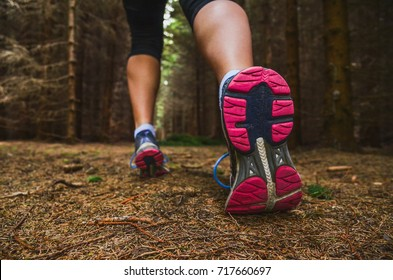 Sole of running shoe in dark forest - run, sport active concept photo