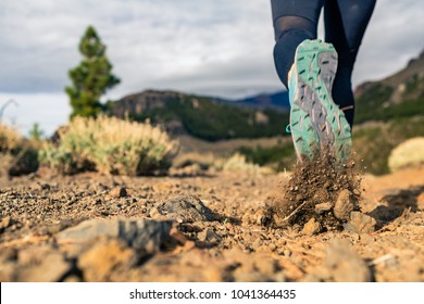 Sole of sports shoe walking in mountains on rocky path. Cross country runner training in inspiring nature, dirt footpath on Tenerife, Canary Islands Spain.