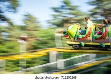 Solec Kujawski, Poland -  August 2017 : Caterpillar shaped rollercoaster train in funpark in dinosaur Park