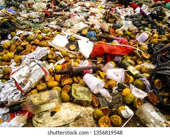 Soledade, Paraíba/Brazil - April 1, 2019: Orange fruits consumed and in a state of decomposition with bottles of beer, plastics and paper in the dump. photo taken in the dump of Soledade, Brazil.