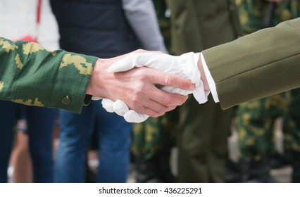 Solemn handshake of men in military clothes