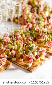 solemn happy new year banquet. Lot of glasses champagne or wine on the table in restaurant. buffet table with lots of delicious snacks. canapes, bruschetta, and little desserts on wooden plate board