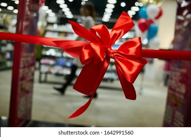 Solemn red ribbon with a bow at the opening of a store / supermarket / shopping center / office. Solemn cutting of the red ribbon. Grand opening of the store. red ribbon with bow