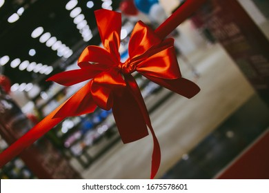 Solemn red ribbon with a bow at the opening of a store / supermarket / shopping center / office. Solemn cutting of the red ribbon. Grand opening of the store. vintage photo processing