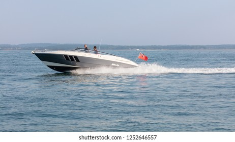 The Solent, Hampshire, England; 7th July 2018; Two Men Aboard a Speedboat Travelling on the Water at High Speed