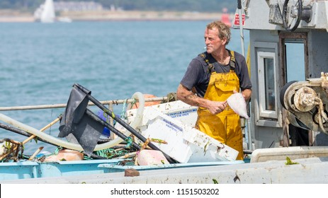 The Solent, Hampshire, UK; 7th August 2018; Closeup of Fisherman Gutting a Fish Whilst Aboard a Small Fishing boat at Sea.