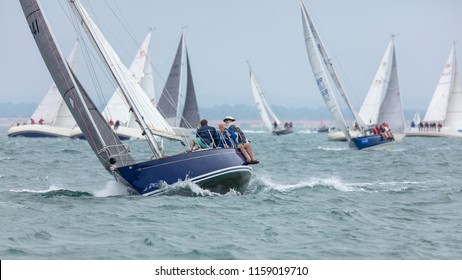 The Solent, Hampshire, UK; 7th August 2018; View Towards Bow of Heeled Yacht Racing at Cowes Week Regatta With Crew Sitting on Side of Boat.  Many Other Yachts Behind