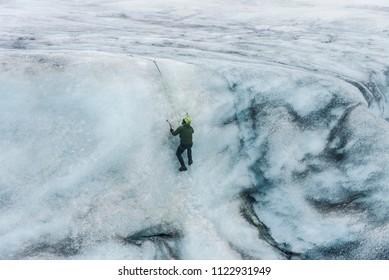 SOLHEIMAJOKULL, Iceland - May 30, 2018: A man climbs an ice cliff on Sólheimajökull Glacier using climbing equipment.