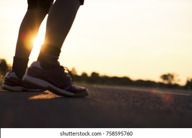 Solhouette of foot running on road in healthy and winner