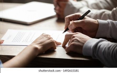 Solicitor pointing at insurance contract showing male client where to write signature sign sale purchase employment agreement at meeting make financial business deal, bank loan service, close up view