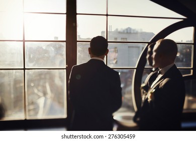 solid brunette groom in  black suit indoor sunlight