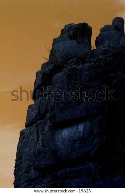 Solid granite rock face silhouetted against evening sky illustrates stability and strength.