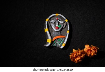 Solid made idol of a female hindu goddess Durga with dry flowers in black copy space background