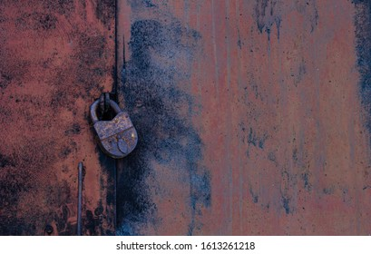 A solid old rusty iron door with a large old padlock with traces of orange and black paint.