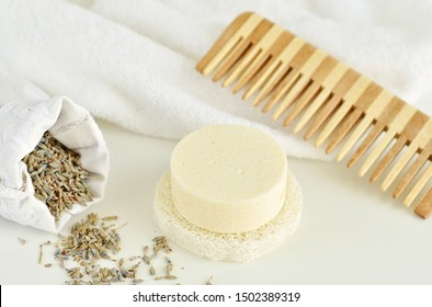 Solid shampoo bar with lavender, wooden hair comb and white towel on background, zero waste bathroom