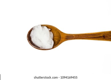 Solid virgin coconut oil or copra oil, is an edible oil. On brown wooden spoon isolated on white. Substitute for shop creams concept.
