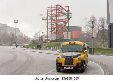 Solihull Birmingham West Midlands England UK March 17th 2019 Bright yellow traditional black taxi cab at the National Exhibition Centre in strong hail storm with tower in background