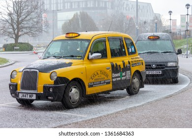 Solihull Birmingham West Midlands England UK March 17th 2019 Bright yellow traditional black taxi cab at the National Exhibition Centre in strong hail storm which is typical English weather