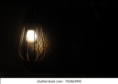 A solitary antique style incandescent bulb shining a golden yellow glowing light in a dark room. Photo in landscape orientation and object on the left side.