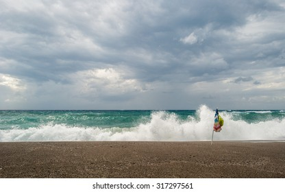 Solitary beach umbrella on the beach during a wind storm with rough sea in the background