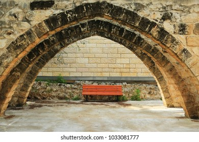 A solitary bench in the middle of an ancient arch