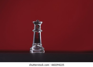 Solitary black chess piece in genuine ebony wood in focus standing on a glossy table in the dark