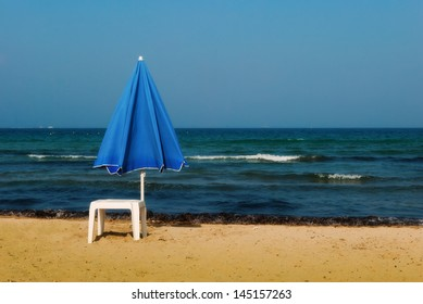 A solitary blue beach umbrella and a white plastic table on a sandy beach close to the water's edge.