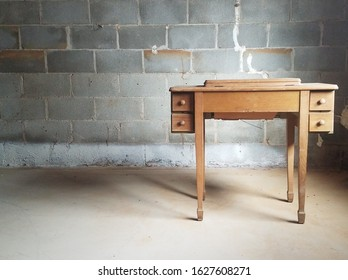 Solitary desk with brick wall in basement