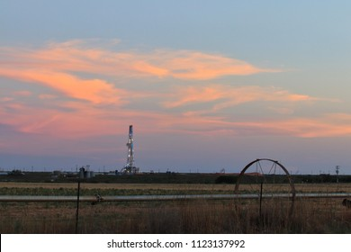 Solitary drilling rig and irrigation equipment at sunset in an agricultural field