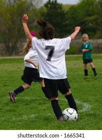 solitary female soccer player arms raised with soccer ball