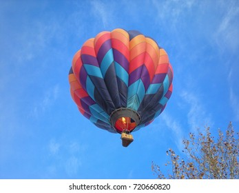 Solitary hot air balloon overhead against blue sky with burner flame engaged