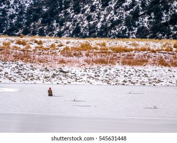 Solitary ice fisherman kneeling at a hole in the ice with fishing rod