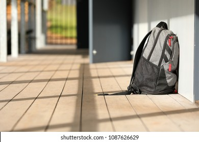 solitary lone grey backpack school bag duffle bag on the ground outside a grey classroom in the hallway. Education, learning, school, study concept. students at work. school yard. back to school.