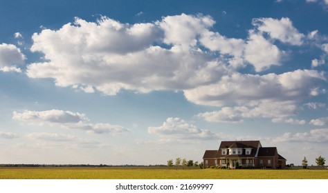 Solitary lonely  house sits by itself on large field with blue sky and clouds.