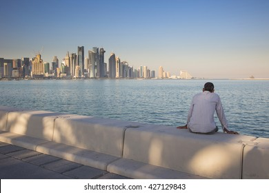 A solitary man sits on a wall late afternoon and admires the West Bay skyline on the Corniche in Doha in Qatar in Arabia with dappled sunlight on the wall.