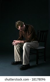 solitary man sitting on chair with head down as if sad or depressed