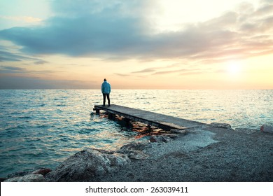 Solitary man stand on boardwalk observing the sea
