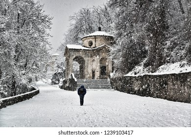 solitary man walking under the snow on the Sacred Way trough the forest with chapel on the right