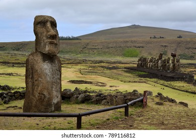 A solitary moai sits in front of Ahu Tongariki, with its many moai looking inward from the coast. The Rapa Nui believed the moai would protect them using their stored mana, or spiritual energy.