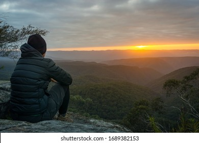 Solitary person sitting and enjoying the sunrise from Splendour Rock, Blue Mountains, NSW, Australia