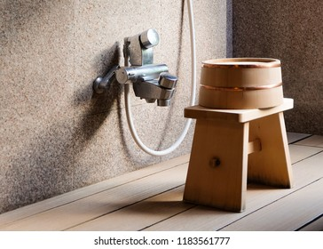 A solitary stool and bucket sit in the light with long shadows next to a shower hose at an onsen in Kyoto, Japan.