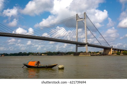 Solitary wooden boat on river Hooghly with the Vidyasagar Setu bridge as the backdrop. The longest cable bridge in India connecting the city of Kolkata with the Howrah district.