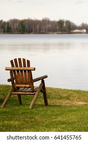solitary wooden chair on the shoreline of a peaceful lake